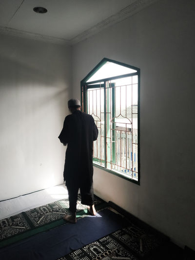 Rear view of man standing against wall at mosque