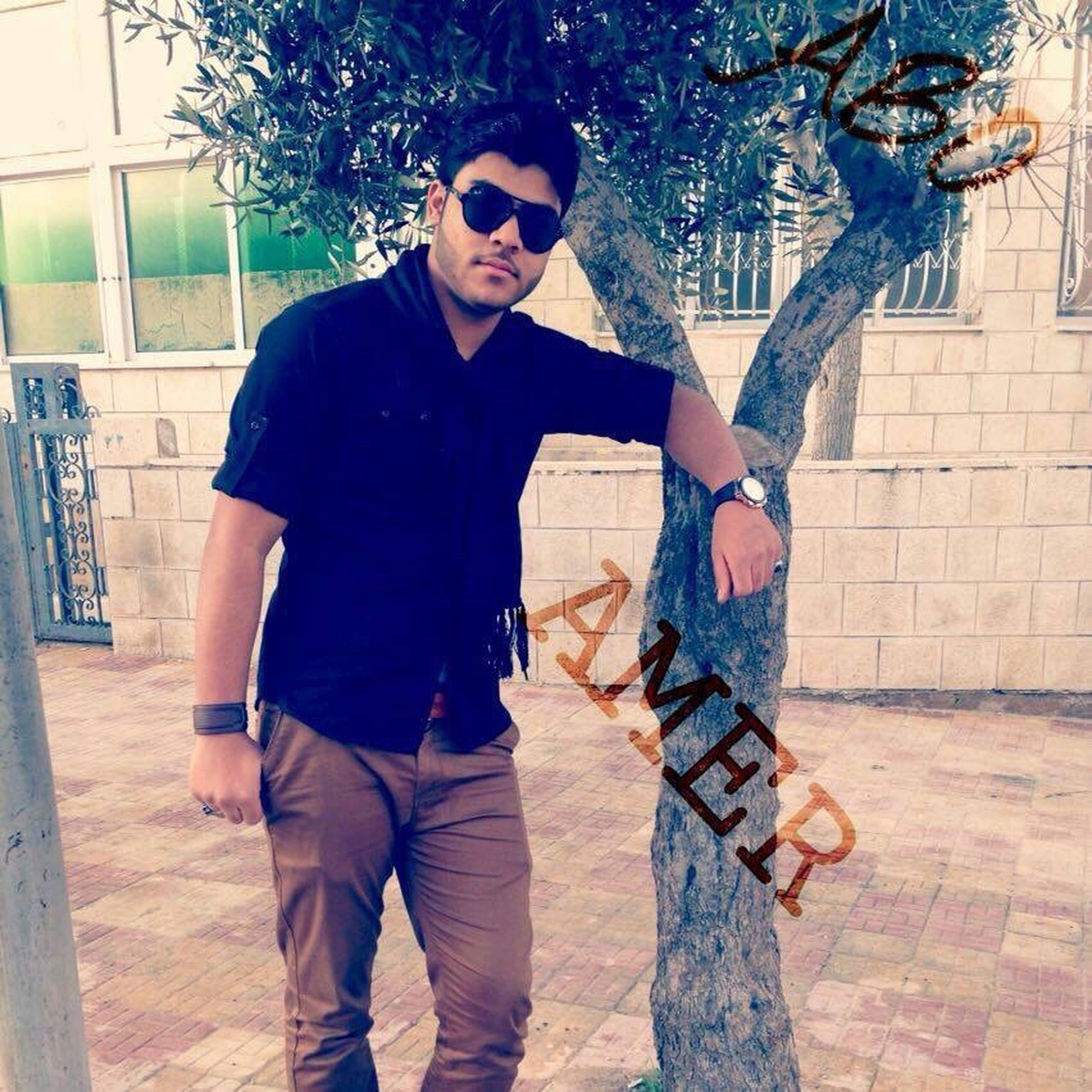young adult, lifestyles, casual clothing, front view, person, looking at camera, standing, portrait, young men, leisure activity, three quarter length, wall - building feature, building exterior, full length, sunglasses, hands in pockets, smiling