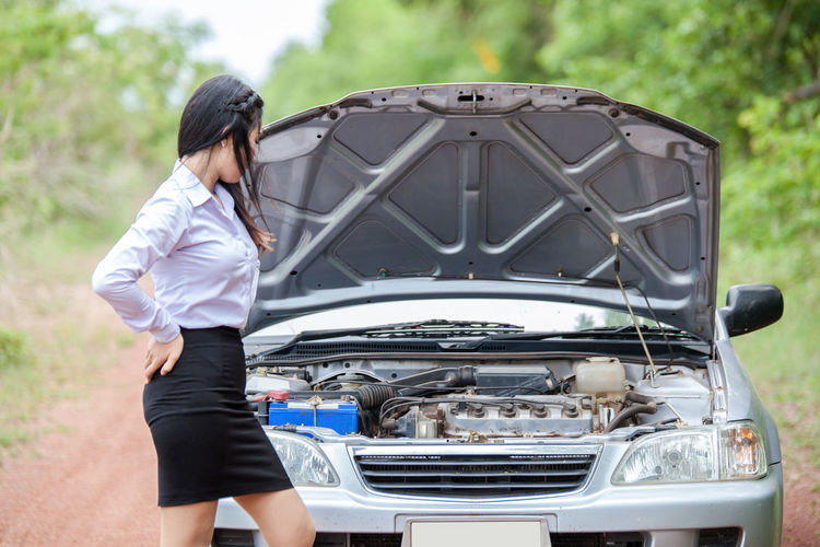Businesswoman Looking At Car Engine