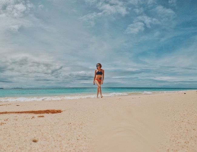 Woman on the beach. Beach Sea One Person Vacations Sand Shirtless Sky Young Adult Leisure Activity Cloud - Sky Lifestyles Real People Full Length Horizon Over Water Water Nature Front View Beauty In Nature Standing Day Bikini Woman Portrait Woman In Bikini Summer Summertime EyeEmNewHere
