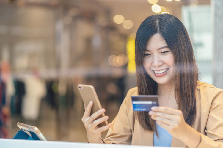 Close-up of smiling woman holding credit card while using mobile phone