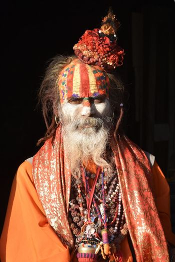 Portrait of a saddhu priest against black background