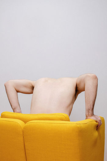Rear view of woman sitting on sofa against wall