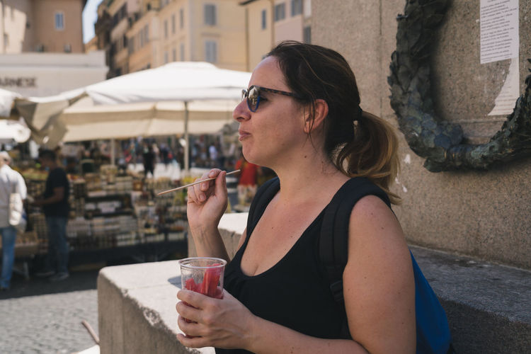 Side view of woman wearing sunglasses eating food outdoors