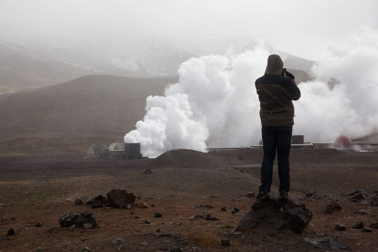 Tourist Photographing Smoke Emitting From Industry While Standing On Desert