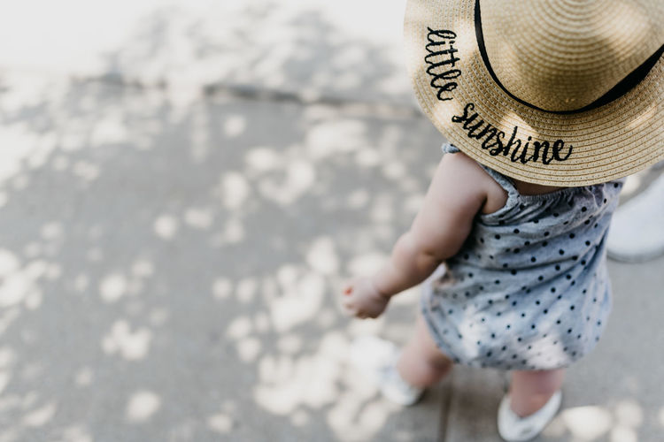 High angle view of baby girl wearing hat outdoors