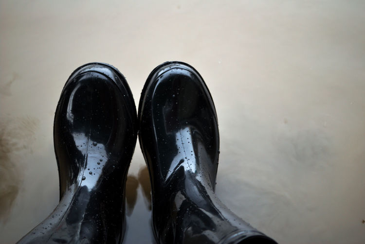 Black boots that enter the time of flooding in the rainy season To prevent germs that come with water and cause diseases such as foot bite disease Black Boot Shoe Protection Foot Boots Treatment Rash Patches Wet Vitiligo Diseases Medical Disease Disorder Dermatology person Illness Skin Sickness Dermatitis Infection Pus Weather Rain Season  Wet Umbrella Climate Storm Monsoon Cloudy Thunderbolt Meteorology Raincoat