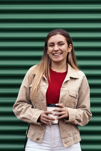 Portrait of smiling woman standing on mobile phone