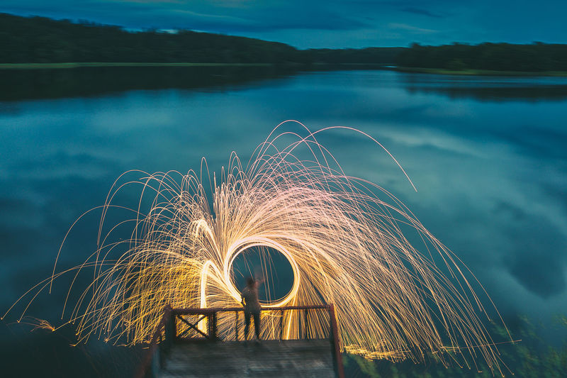 Person making wire wool at lake during dusk