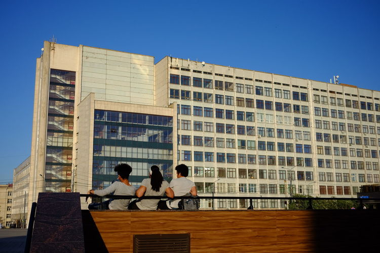 People standing by modern building against clear sky