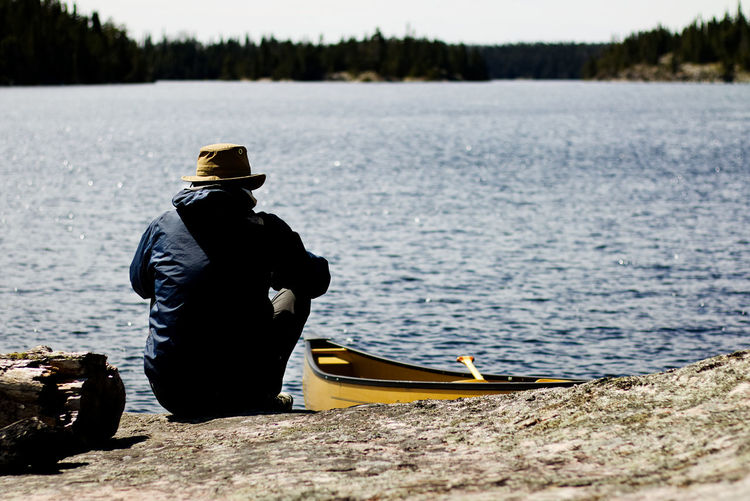 solo canoeing in northern Ontario, Canada. Canoe Canoeing Lakeview Beauty In Nature Hat Lake Lakeside Lifestyles Mammal Men Nature Nautical Vessel One Person Outdoors Paddle Paddling People Real People Rear View Solo Solo Canoeing Spring Water Yellow
