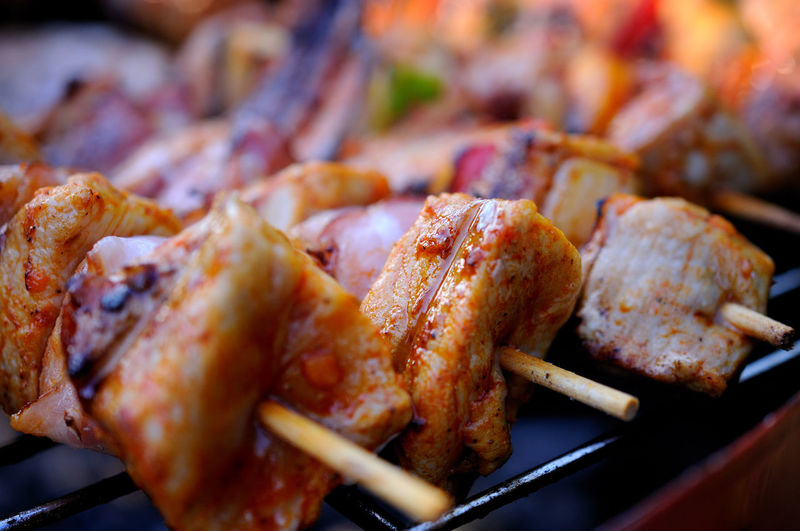 Close-up of meat in skewers on barbecue grill