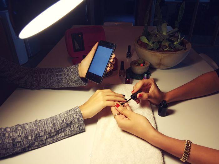 Woman Applying Nail Polish On Hand Of Friend