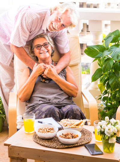 Senior couple embracing while sitting by food on table