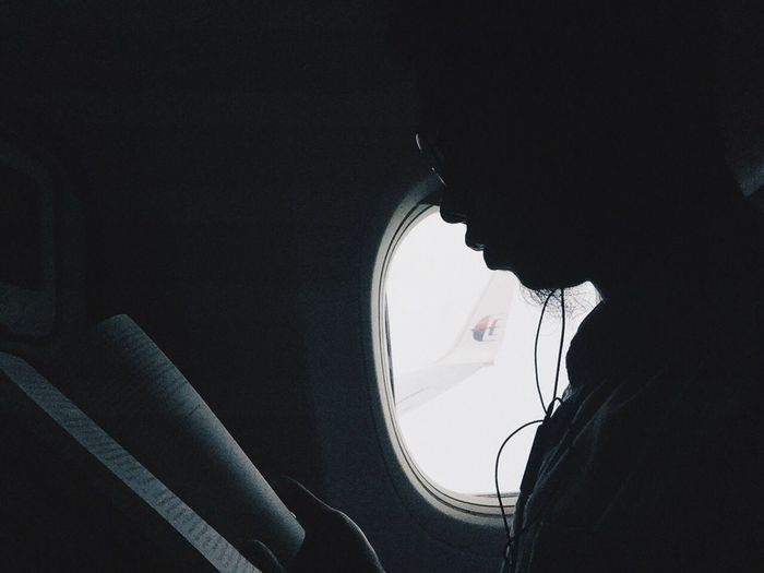 Cropped image of man sitting in airplane