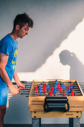 Young teenager boy playing table football with another player. Young people having fun, spending time together Game Players Football Soccer Toy Competition Match Fun Leisure Funny Playing Play Sport Enjoyment Teenager Team Joy Compete Boy Man Competitor Rival Relaxing Real People