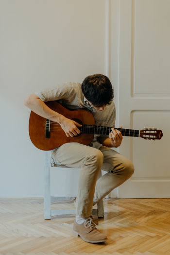 Man playing guitar at home