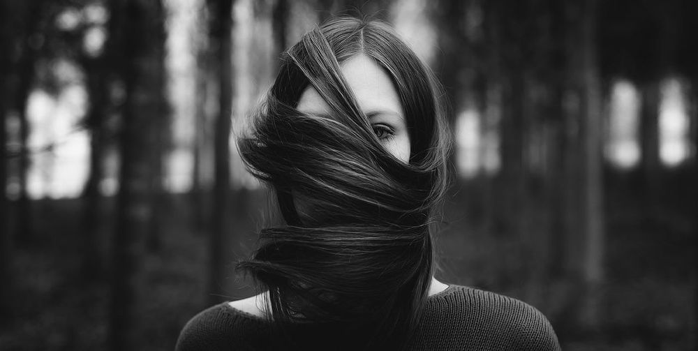 Close-up of woman with hair against trees