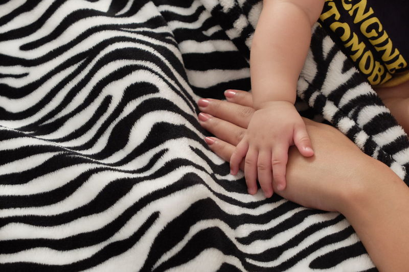 Animal Themes Baby Babyhood Bed Bonding Childhood Close-up Day Human Body Part Human Hand Indoors  Leisure Activity Lifestyles Nail Polish People Real People Striped Togetherness Zebra