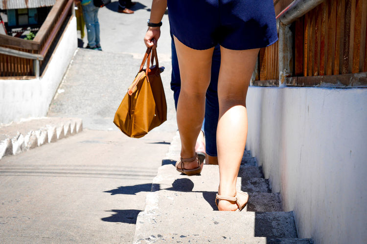 Low section of woman walking on steps outdoors