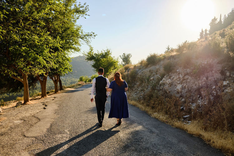 woman and man walk along the road. concept of togetherness and loyalty. walk the road together.