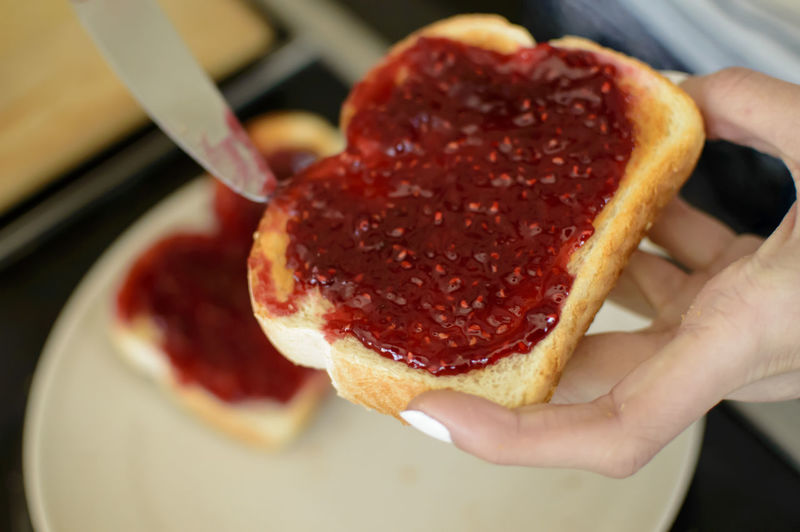 Breakfast Making toast with Fresh Home Made Raspberry Jam Preserves Breakfast Close-up Day Food Food And Drink Freshness Healthy Eating Holding Human Body Part Human Hand Indoors  Meat One Person People Ready-to-eat Red Spreading Toasted Bread Food Stories