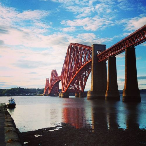 Low Angle View Of Forth Rail Bridge Over River Against Cloudy Sky
