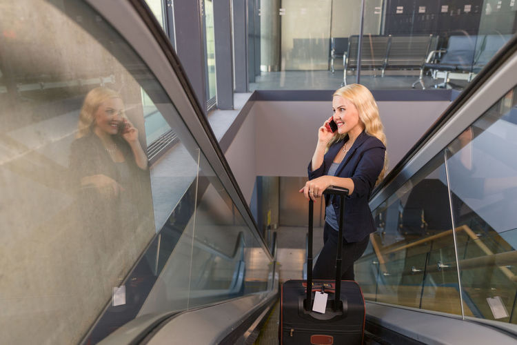 Woman using mobile phone while standing on glass