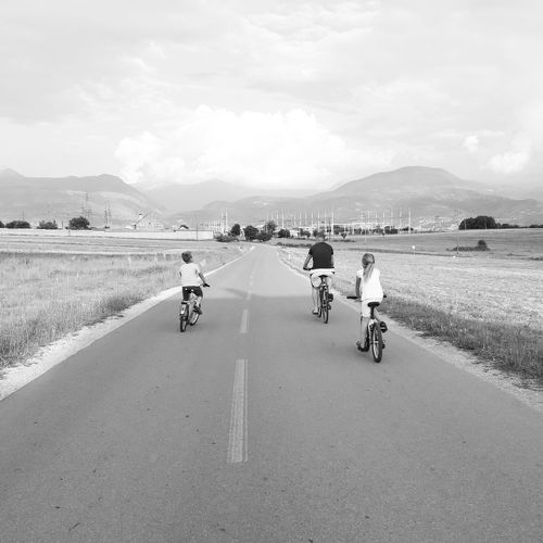 Rear view of father riding bicycle with children on road