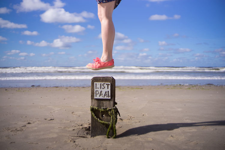 Scenic View Of Woman Jumping At Beach
