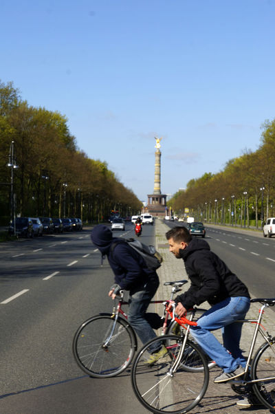 Architecture Berlin Bicycle Built Structure City City Life Cycling Day Land Vehicle Leisure Activity Lifestyles Men Mode Of Transport Outdoors Real People Riding Road Sky Straße Des 17. Juni Tourism Transportation Travel Travel Destinations Two People