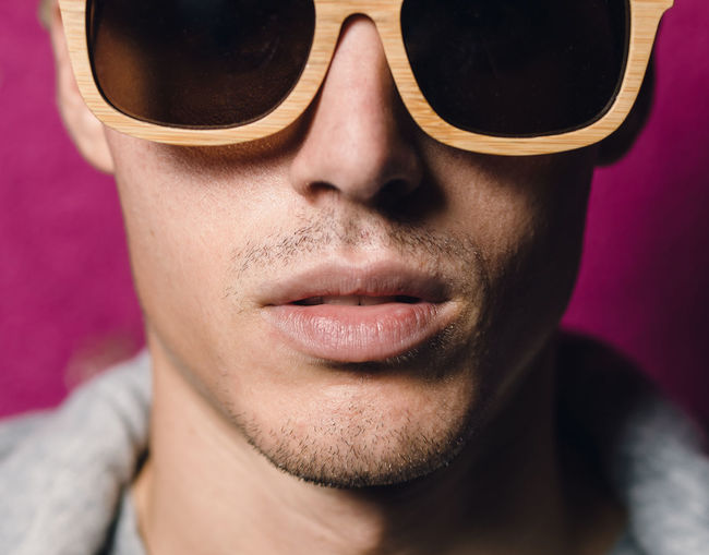 Portrait Of Man Wearing Sunglasses Against Pink Wall