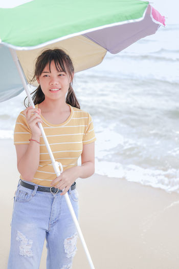 Woman holding umbrella while standing on beach