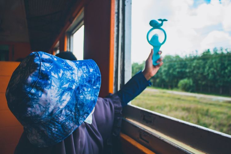 Close-up of woman holding toy at window of train