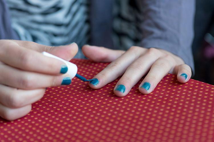 Midsection of woman applying nail polish at table