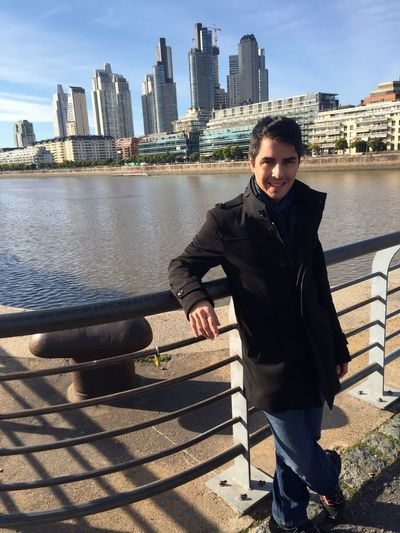Portrait of smiling man leaning on railing against river
