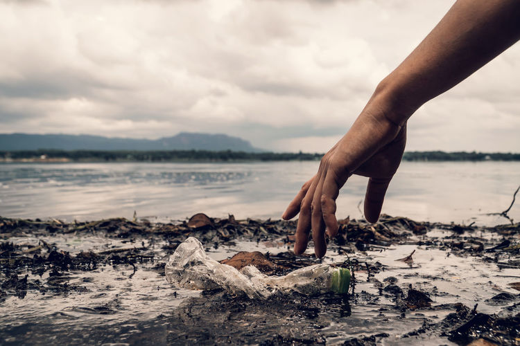 Cropped hand picking plastic bottle from shore at beach against cloudy sky