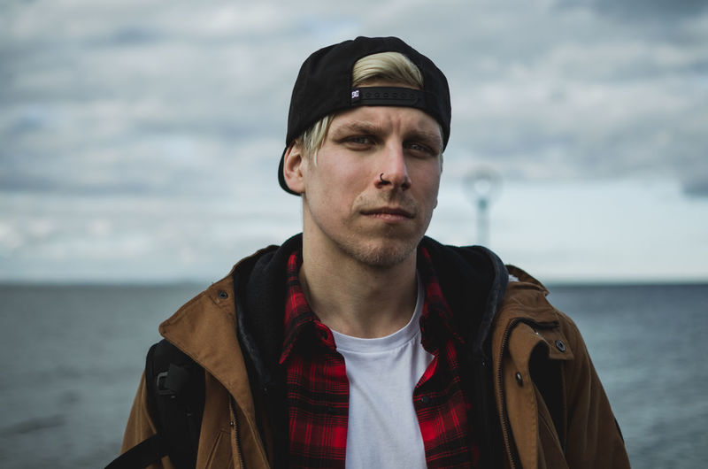 Portrait of young man standing at sea shore