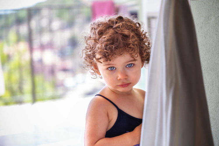 Portrait of girl standing by curtain