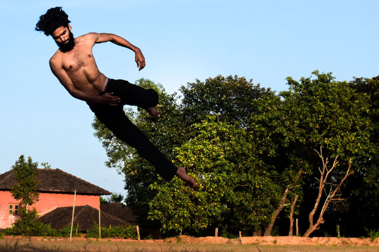 Low angle view of shirtless man jumping against trees