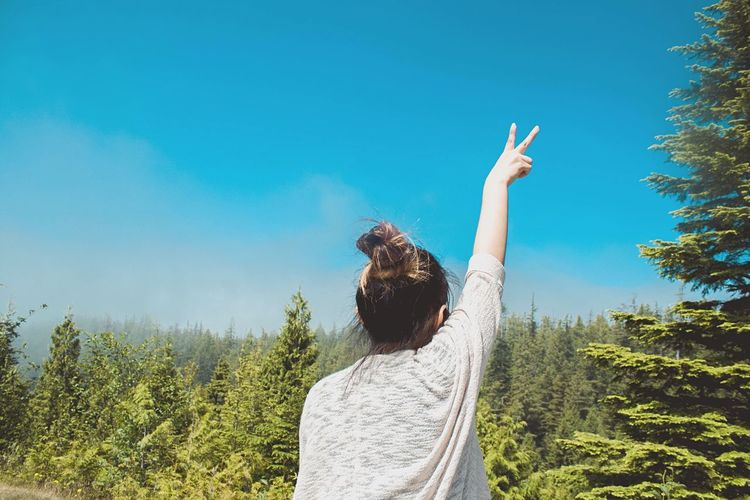 Rear view of woman with peace sign against blue sky