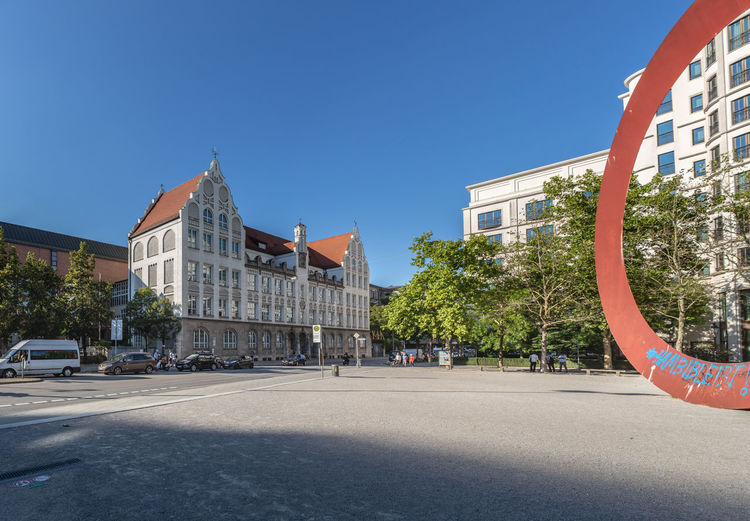 MUNICH, BAVARIA, GERMANY - CIRCA SEPTEMBER, 2018: Marienplatz in Munich, Germany. Marienplatz In Munich, Munich, Architecture, Bavaria, Destination, Europe, European, Germany, Historical, House, Location, Moody, Old, Outdoors, Sightseeing, Sport, Sunlight, Tourism, Travel, Trees, Vintage, Visitor, Wall, Window, Built Structure Architecture Building Exterior Sky Building City Blue Clear Sky Transportation Street Nature Road Day Tree Sunlight Motor Vehicle Plant Copy Space Residential District Car No People