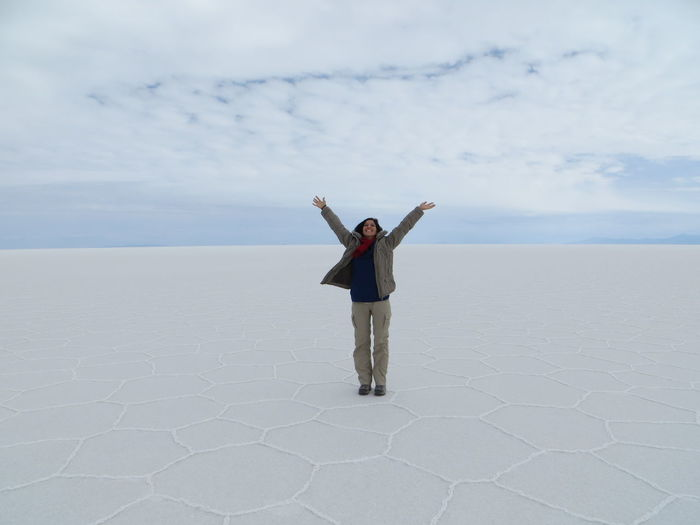 Excited Woman Standing With Arms Raised On Salt Flat At Salar De Uyuni Against Sky