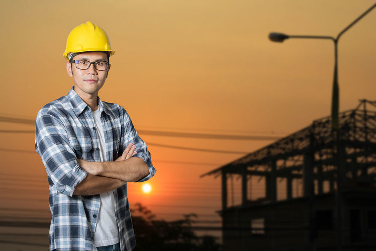 Day Front View Hardhat  Headwear Looking At Camera Men Nature One Person Outdoors People Portrait Protective Workwear Real People Sky Smiling Standing Sunset Yellow Young Adult