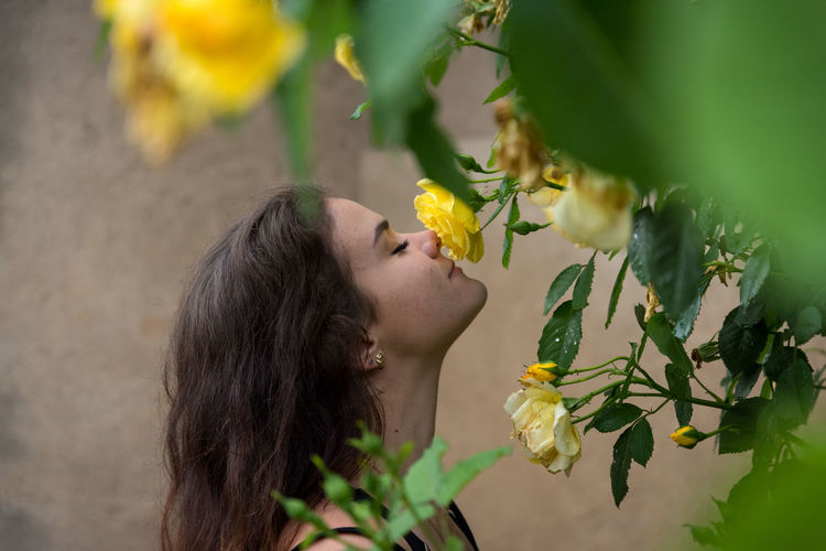 Side View Of Woman Smelling Yellow Flower