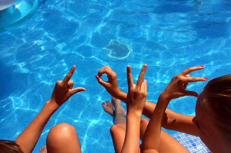 High angle view of girls gesturing while sitting in swimming pool