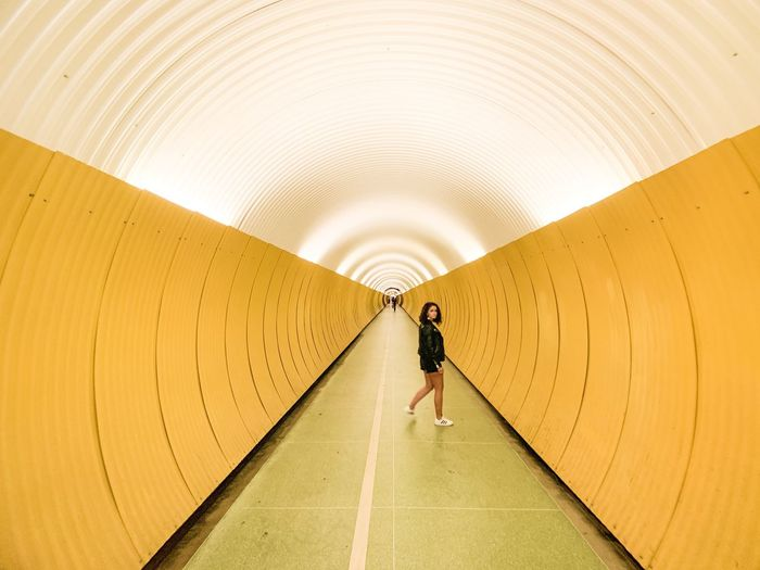 Full length of woman walking in tunnel
