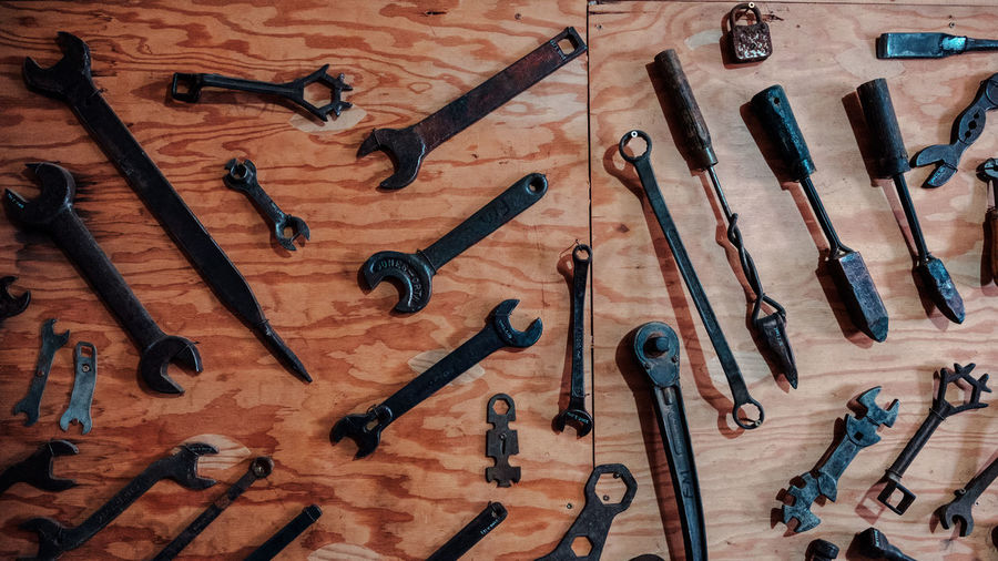 Black tools arranged on wooden wall