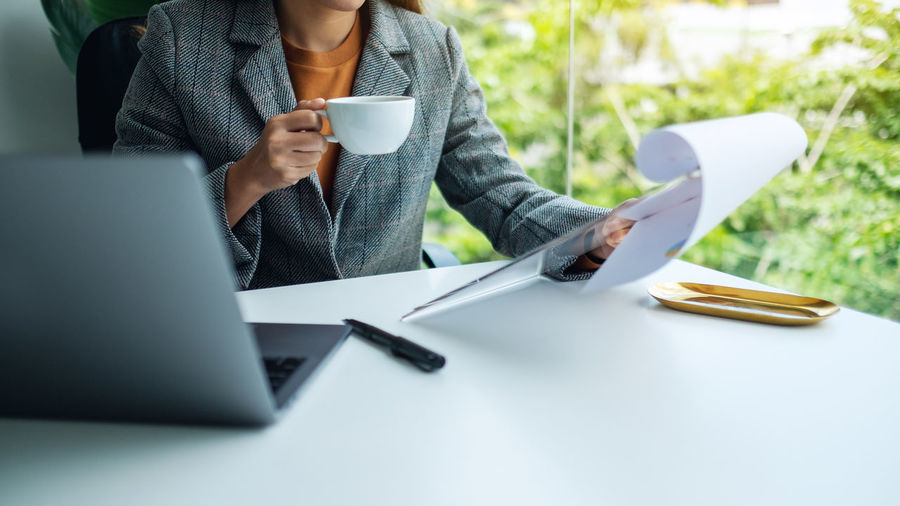 Midsection of woman holding coffee while sitting on table