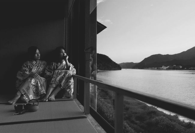 Japanese Culture Adult Architecture Black Full Length Kimono Leisure Activity Lifestyles Looking At View Men Mountain Nature Outdoors People Positive Emotion Railing Real People Rear View Sitting Sky Togetherness Two People Water Women